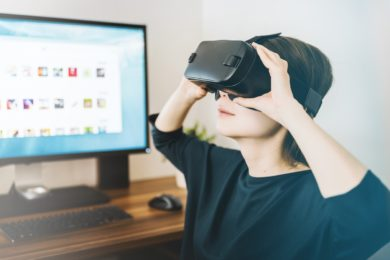 Woman sitting at desk with a virtual reality headset on.