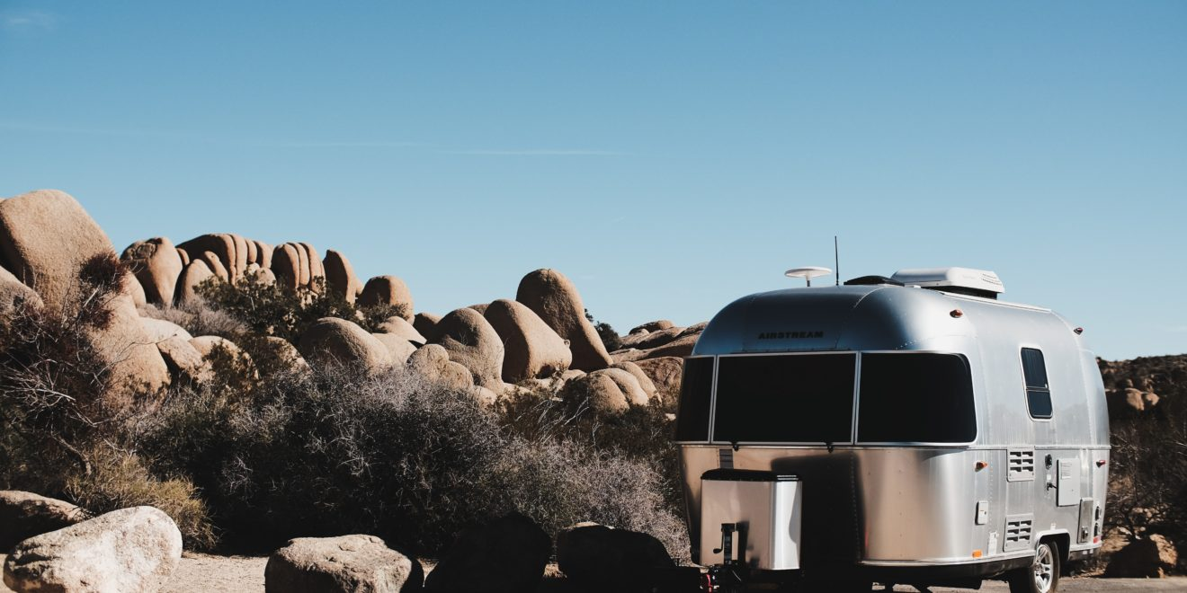 An RV sitting by some rocks